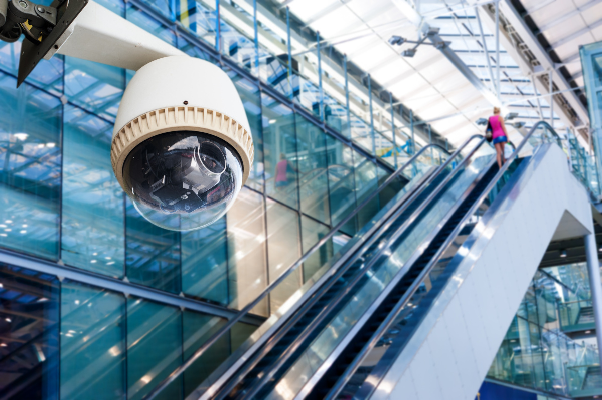 Close Up of Surveillance Camera with Woman on Escalator in Background
